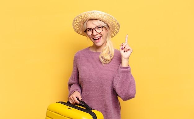 アイデアを実現した金髪女性が元気に指を上げて、幸せでワクワクする天才、エウレカ!