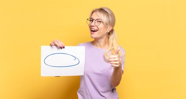 Блондинка чувствует себя гордой, беззаботной, уверенной и счастливой, позитивно улыбается, показывает палец вверх