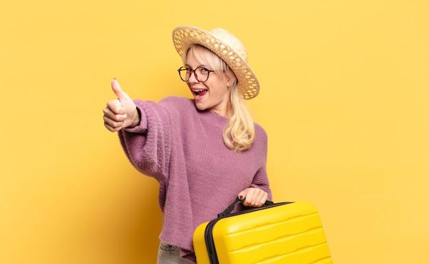 자랑스럽고, 평온하고, 자신감 있고, 행복하고, 엄지 손가락으로 긍정적으로 웃고있는 금발의 여인