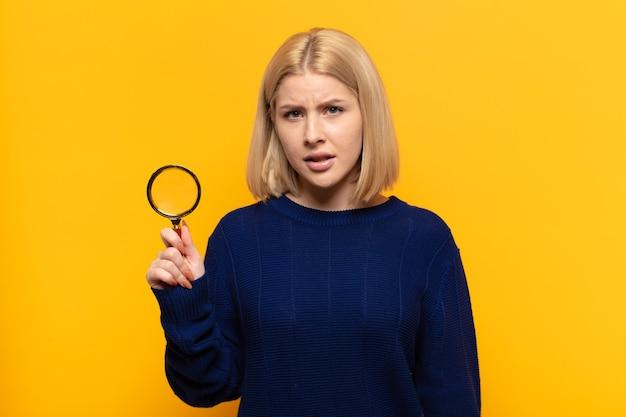 Блондинка недоумевает и смущена, с тупым, ошеломленным выражением лица смотрит на что-то неожиданное