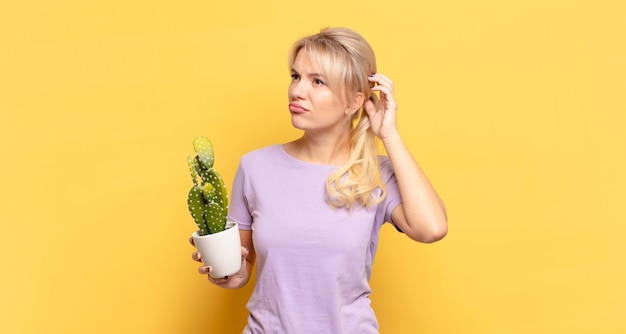 Blonde woman feeling puzzled and confused, scratching head and looking to the side