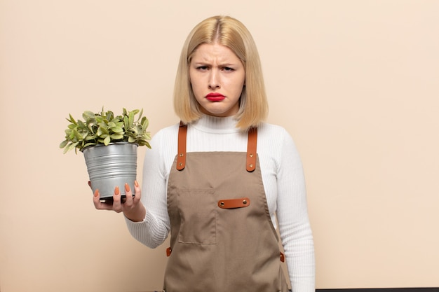 Blonde woman feeling sad and whiney with an unhappy look, crying with a negative and frustrated attitude
