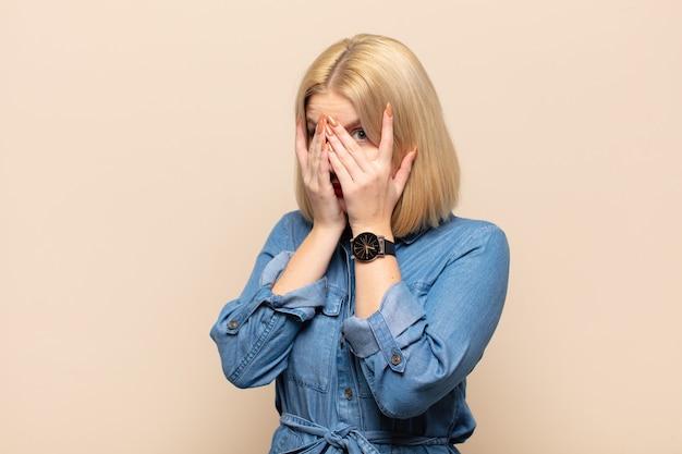 Блондинка чувствует себя напуганной или смущенной, подглядывает или шпионит с полузакрытыми руками глазами