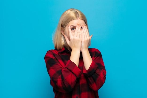 Блондинка чувствует себя напуганной или смущенной, подглядывает или шпионит с полуприкрытыми руками глазами