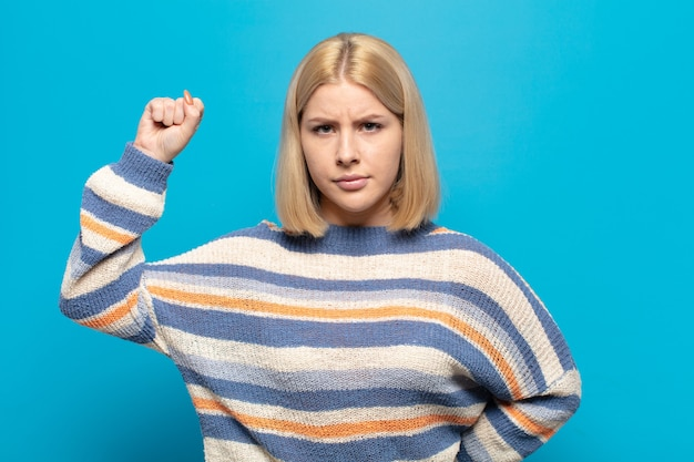 Blonde woman feeling serious, strong and rebellious