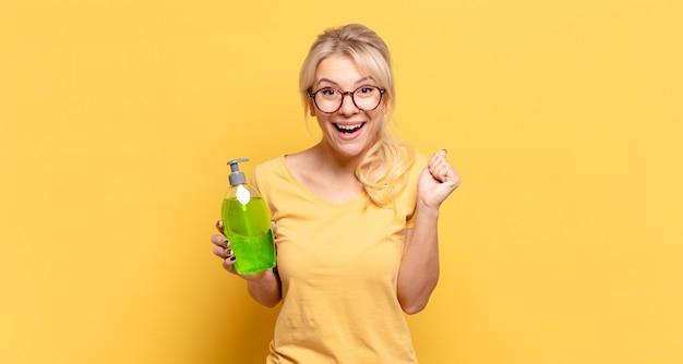 금발의 여인은 충격을 받고 흥분하고 행복하며 웃고 성공을 축하하며 와우라고 말합니다!