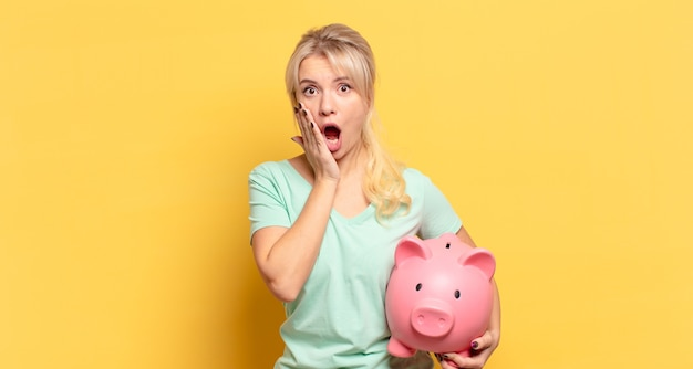 Blonde woman feeling shocked and scared, looking terrified with open mouth and hands on cheeks