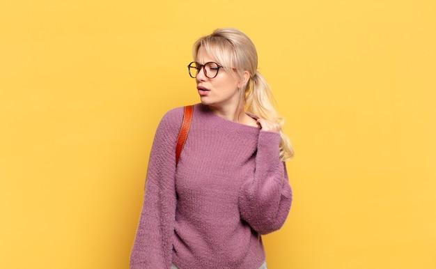 금발의 여인은 스트레스, 불안, 피곤하고 좌절감을 느끼고 셔츠 목을 당기고 문제로 좌절감을 느낍니다.