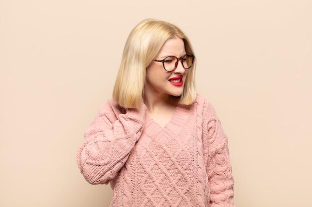 Блондинка чувствует себя подчеркнутой, расстроенной и усталой, потирая болезненную шею, с встревоженным и встревоженным взглядом