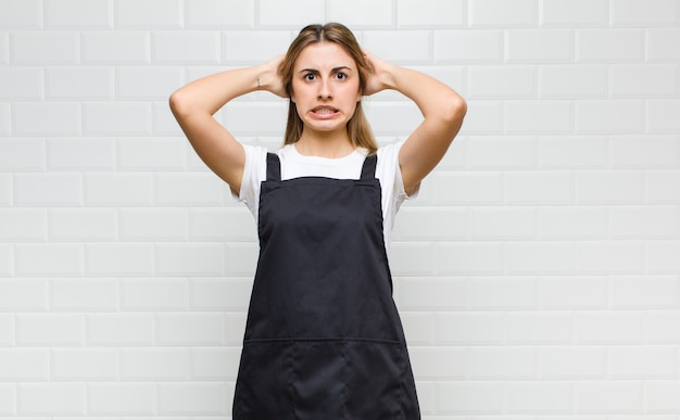 Blonde woman feeling stressed, worried, anxious or scared, with hands on head, panicking at mistake