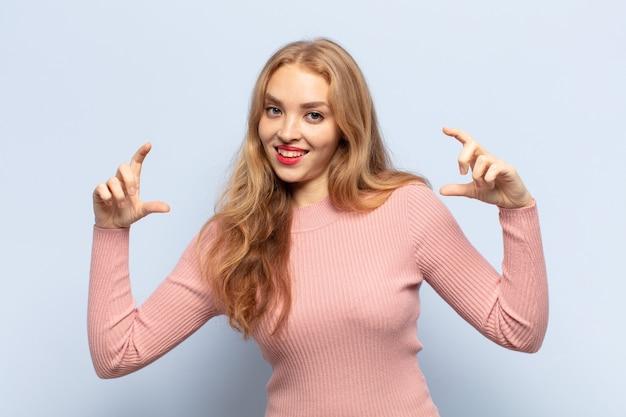 Светловолосая женщина, обрамляющая или очерчивающая собственную улыбку обеими руками, выглядящая позитивно и счастливой, концепция благополучия