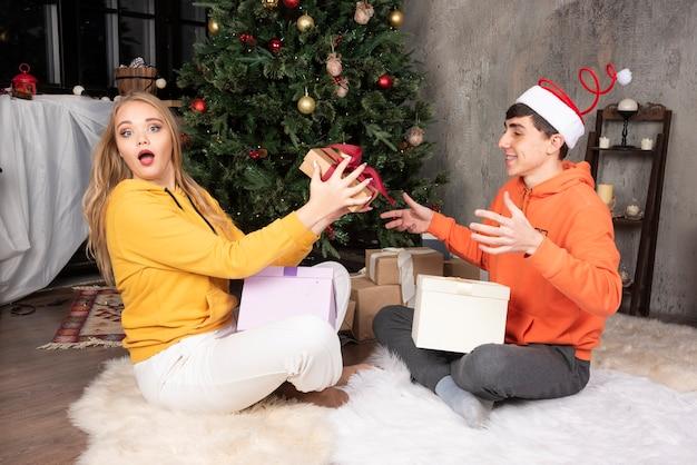 금발의 여자는 크리스마스 트리 근처에서 남자 친구로부터 선물을 받고 흥분합니다.