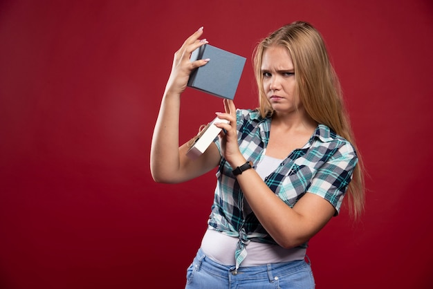 ブロンドの女性は、ギフトボックスを開いている間、悲しくて混乱します。
