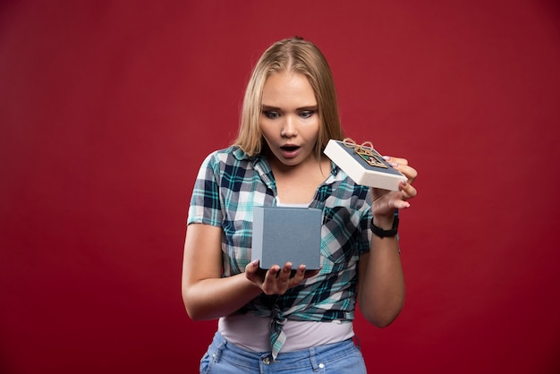 金髪の女性は、ギフトボックスを開いているときに驚いています。