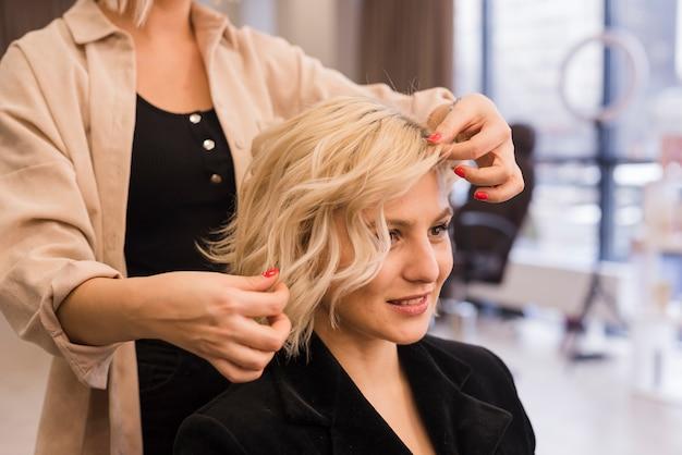 Блондинка делает прическу Premium Фотографии