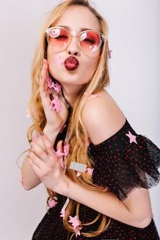 Donna bionda che dà bacio, divertirsi alla festa, evento di celebrazione, ricoperta di coriandoli. indossa occhiali rosa, un bel vestito nero, ha i capelli lunghi.