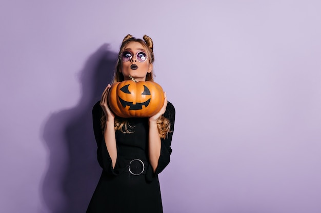 Blonde woman in glasses holding halloween pumpkin.  photo of worried young witch.