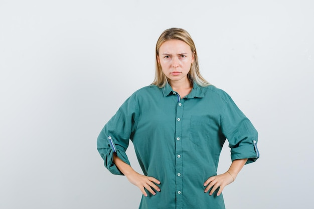 Donna bionda in camicia verde che si tiene per mano sulla vita e sembra seria