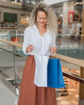 Donna bionda felice dopo lo shopping nei centri commerciali