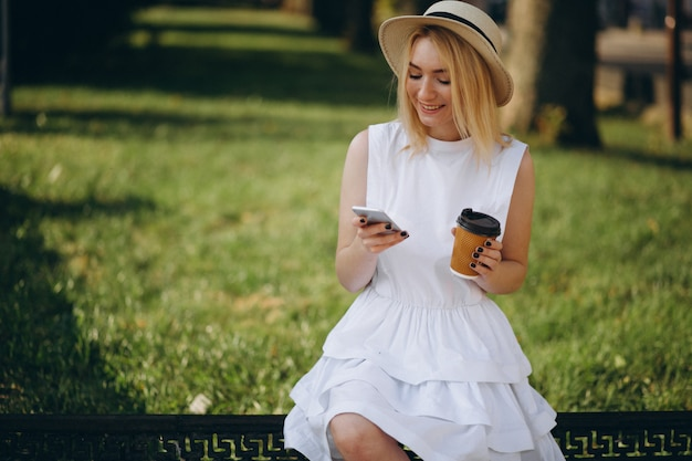 Blonde woman in hat using phone and drinking coffee