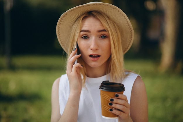Blonde woman in hat using phone