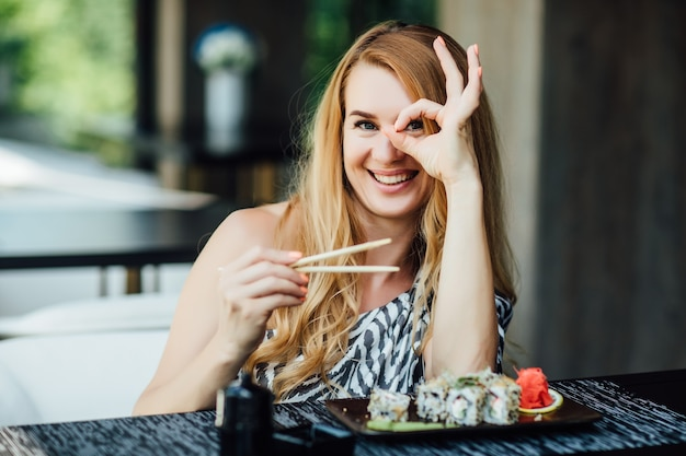 Blonde woman have a sushi time in restaurant