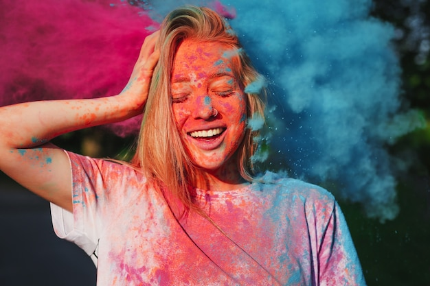 Blonde woman having fun with exploding blue and pink dry powder celebrating holi festival