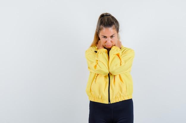 Блондинка с болью в шее в желтой куртке-бомбардировщике и черных штанах выглядит усталой