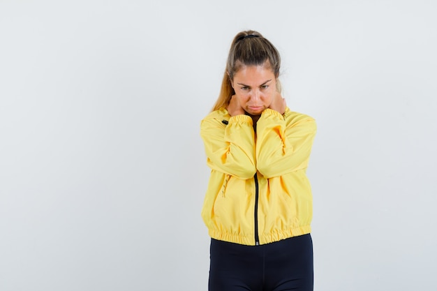 Donna bionda che ha dolore al collo in bomber giallo e pantaloni neri e sembra stanca