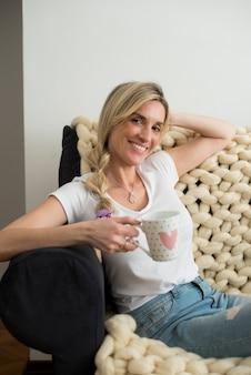 ソファでお茶を飲んでいる金髪の女性