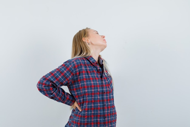 Блондинка с болью в пояснице в клетчатой рубашке выглядит измученной. передний план.