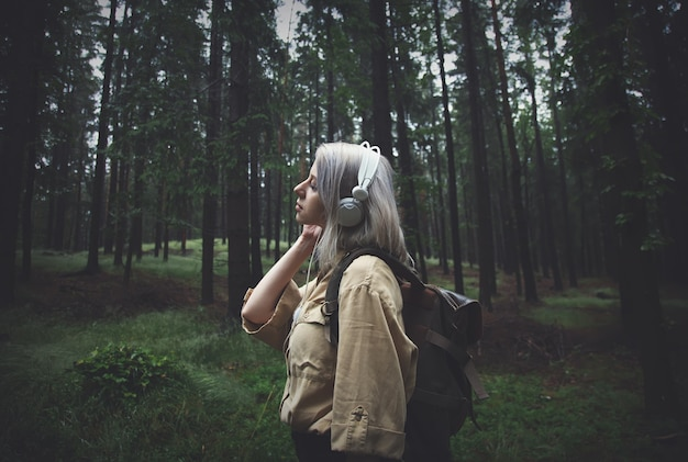 Blonde woman in headphones with backpack in rainy day in forest
