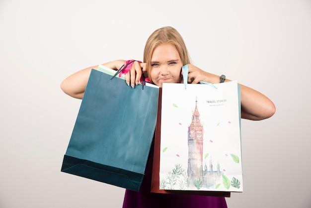 Donna bionda che si nasconde dietro le borse della spesa.
