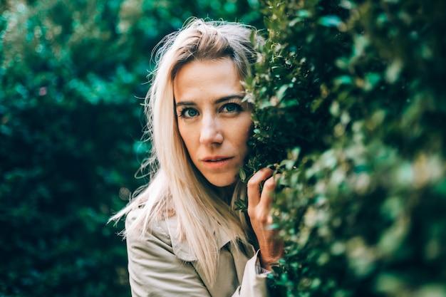 Blonde woman hiding behind some vegetation.