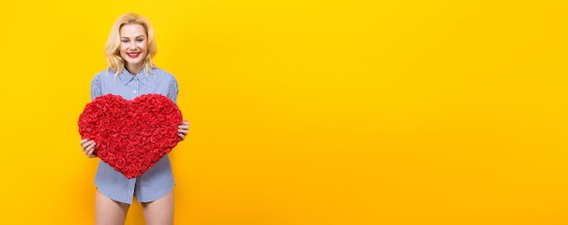 Blonde woman hold big red flower heart. horizontal background