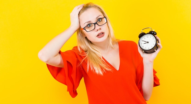 Blonde woman holding alarm clock