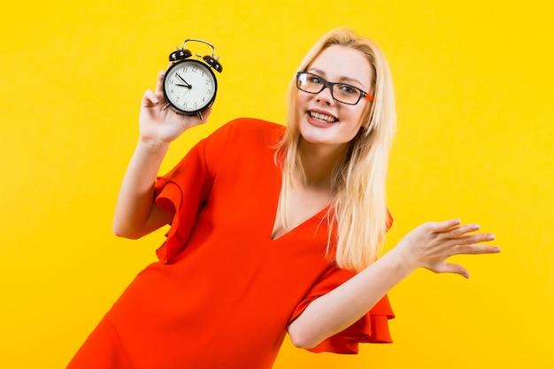 目覚まし時計を保持している金髪の女性