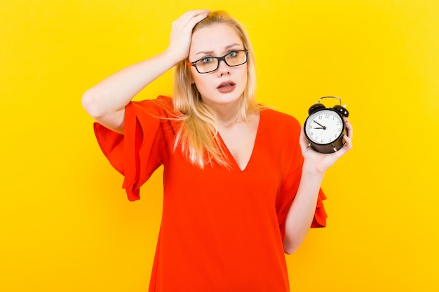 Blonde woman holding alarm clock