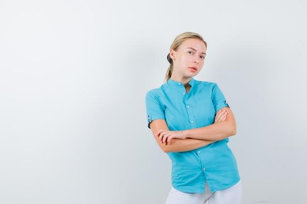 青いブラウスに腕を組んで、自信を持って孤立して見える金髪の女性
