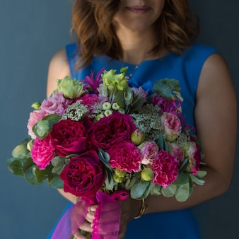Blonde woman holding a bouquet of peonies.