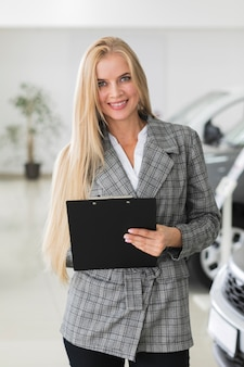Blonde woman holding a clipboard