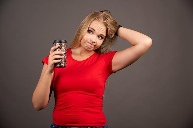 Donna bionda che tiene alla tazza di caffè sulla parete nera.