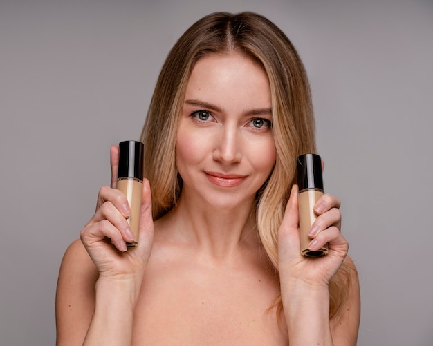 Blonde woman holding a foundation bottles