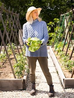 Donna bionda che tiene cavolo verde fresco in sue mani