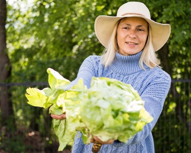 Donna bionda che tiene un cavolo verde