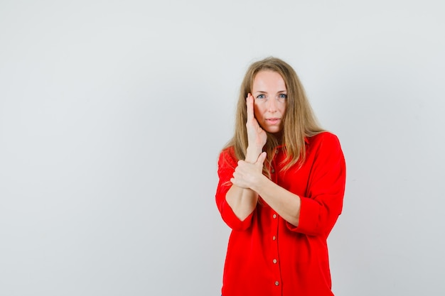 Donna bionda che tiene la mano sulla guancia in camicia rossa e sembra sbalorditiva.