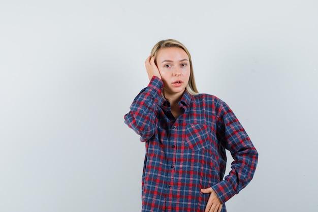 耳に手を押しながら腹に手をつないで、チェックのシャツを着てカメラに向かってポーズをとって驚いた金髪の女性。正面図。