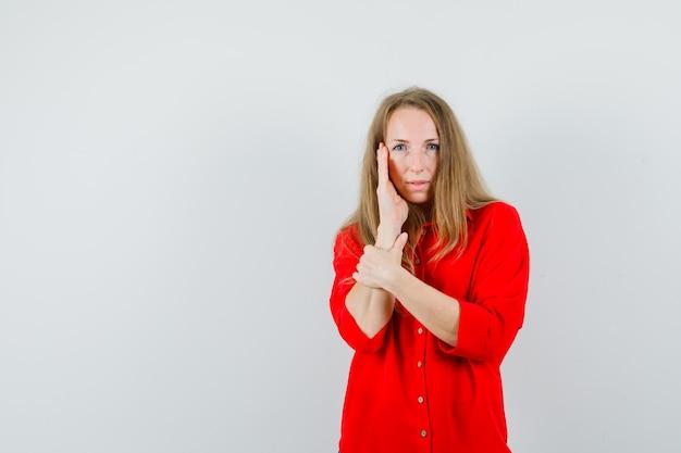 赤いシャツを着て頬に手をつないで見事に見える金髪の女性。