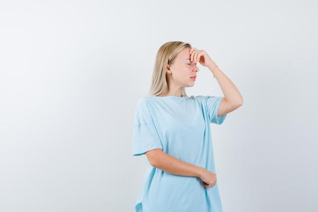 頭に手を握って、青いtシャツで頭痛があり、疲れているように見える金髪の女性