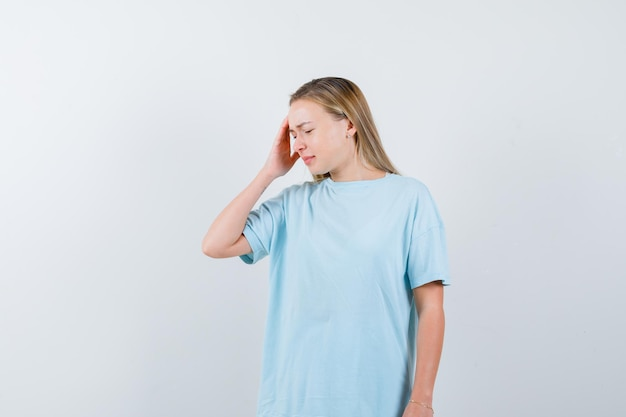 Блондинка держит руку на храме в синей футболке и выглядит мило